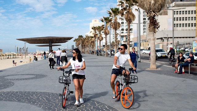Ciudadanos israelíes pasean en bicicleta por Tel Aviv.