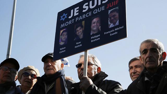 Familiares de las víctimas del ataque contra un supermercado kosher en Paris en 2015 sostienen un cartel durante su funeral.