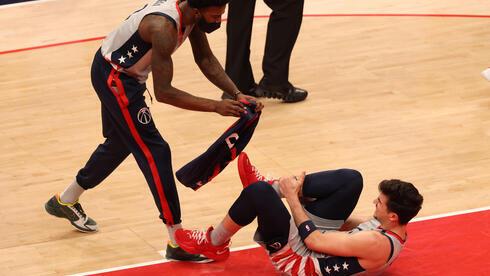 El alero de los Washington Wizards, el israelí Deni Avdija, es asistido por su compañero Jordan Bell después de lesionarse en el partido contra Golden State.