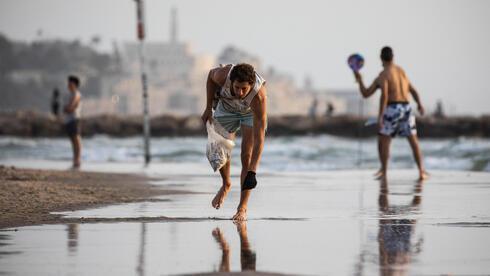 Melcer juntando colillas de cigarrillos en una playa de Tel Aviv.