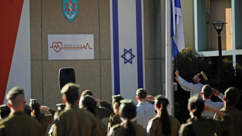 Formación de tropas israelíes mientras la bandera es arriada a media asta durante el día de duelo en Israel.