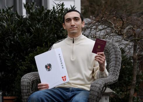 Noah Rohrlich, cuyo abuelo huyó del nazismo en Austria, posa en su casa con su certificado de ciudadanía y un nuevo pasaporte de Austria.