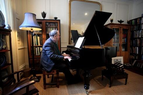 Robert Anderson se sienta al piano centenario vienes que alguna vez perteneció a sus bisabuelos.