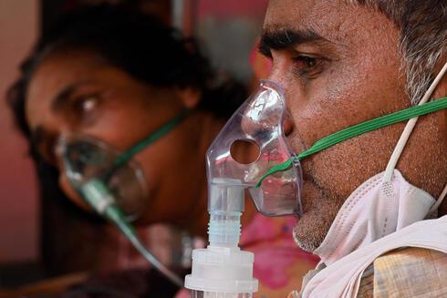 Pacientes enfermos de COVID-19 reciben oxígeno en India.