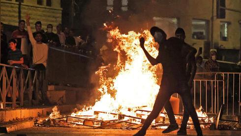 Palestinos arrojan piedras contra las fuerzas de seguridad israelíes en la Puerta de Damasco en Jerusalem.