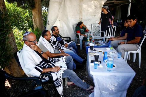 Amigos y familiares de Yigal Yehoshua durante el período de luto posterior a la muerte de Yehoshua, en el Moshav Hadid.