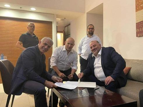 Yair Lapid, de Yesh Atid (izquierda), Naftali Bennett, de Yamina (centro), y Mansour Abbas, de Raam, firman el acuerdo de coalición.