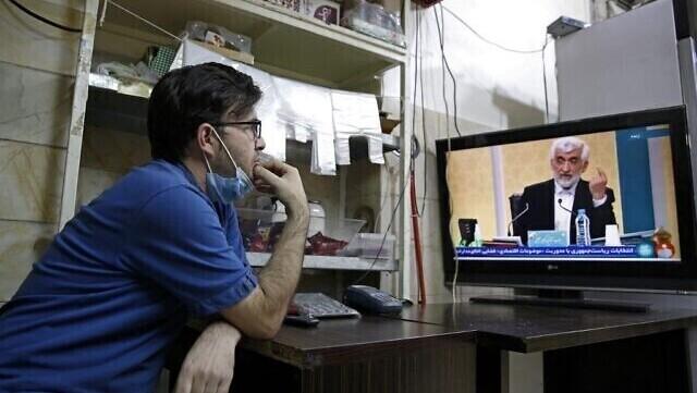 Un ciudadano iraní mira al candidato Saeed Jalili durante el primer debate preelectoral en una tienda de Teherán.