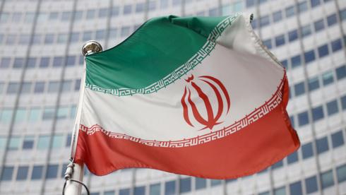 La bandera iraní ondea frente a la sede del Organismo Internacional de Energía Atómica en Viena, Austria.