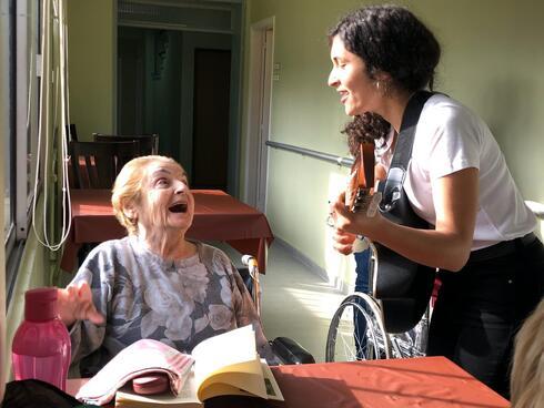 Lucía Abelar canta para una residente de un hogar de ancianos antes de la pandemia.