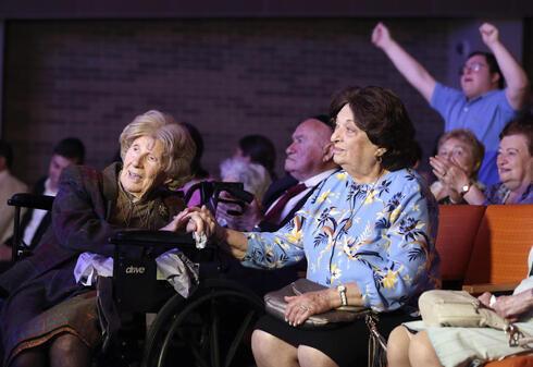 Aranka Engel, de 103 años, sostiene la mano de su compañera sobreviviente del Holocausto Jean Kurz, de 81 años.