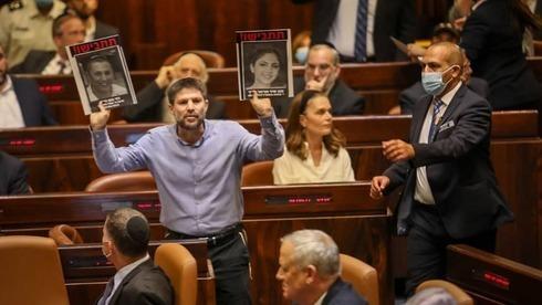 Bezalel Smotrich, líder de Sionismo Religioso, muestra fotos de víctimas del terrorismo durante el discurso de Bennett en la Knesset el domingo.