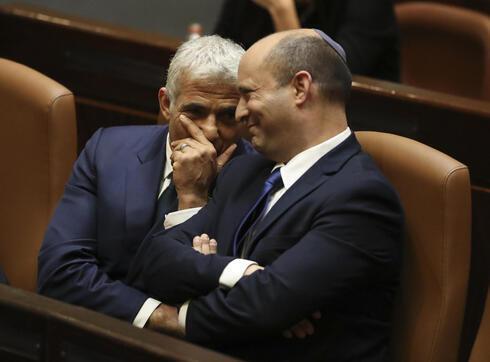 Yair Lapid y Naftali Bennett en la Knesset para la votación del domingo que los convirtió en canciller y primer ministro, respectivamente.
