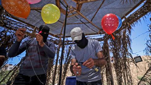 Miembros de la Yihad Islámica preparan globos incendiarios para lanzar hacia Israel.