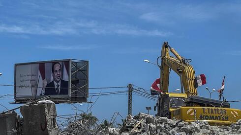 Una excavadora limpia los escombros en Gaza junto a una imagen del presidente egipcio Abdel Sisi, que ha prometido millones de dólares para reconstruir el enclave.