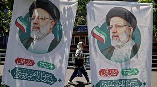 Una iraní pasa entre dos afiches del candidato presidencial Ebrahim Raisi, el 17 de junio de 2021 en Teherán.