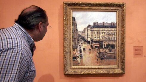 """Un visitante observa en el cuadro impresionista titulado """"Rue St.-Honore, Apres-Midi, Effet de Pluie"""", pintado en 1897 por Camille Pissarro, expuesto en el Museo Thyssen-Bornemisza de Madrid."""