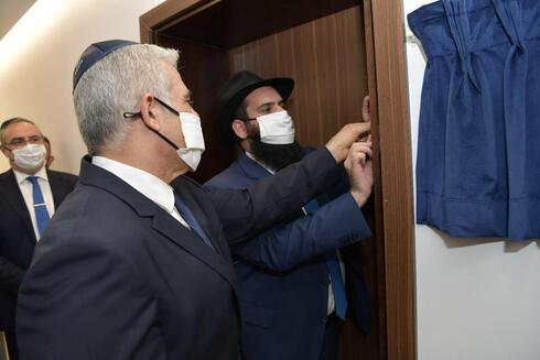 Lapid coloca la mezuzá en la embajada israelí inaugurada en Abu Dhabi.