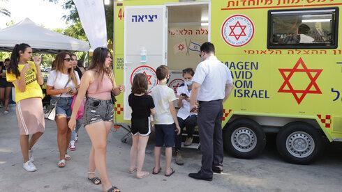 Adolescentes hacen cola frente a un centro de vacunación emergente en Tel Aviv.