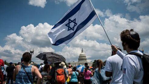 Un hombre sostiene una bandera israelí durante una protesta contra el antisemitismo en Washington.