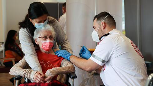 Una adulta mayor de una residencia de ancianos en Netanya sostiene la mano de su cuidador mientras recibe la vacuna contra el coronavirus.