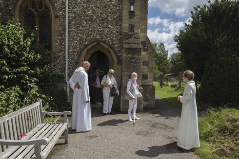 El reverendo Jonathan Gordon y la vicaria asistente Miranda Sheldon saludan a los fieles anglicanos en la iglesia de Santa María, Inglaterra.