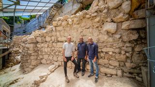 Directores de la excavación junto al segmento de muro encontrado.