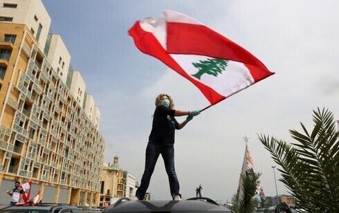 Una mujer libanesa ondea la bandera nacional durante las protestas contra el gobierno en Beirut, abril de 2021.