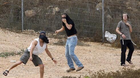 Jóvenes de asentamientos judíos de Cisjordania arrojan piedras contra palestinos.