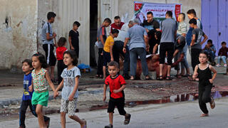 Niños pasean por una calle de Gaza, mientras a sus espaldas sacrifican a un animal en ocasión de Eid Al Adha.