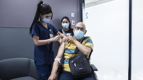 Un adulto mayor recibe una dosis de refuerzo de vacuna contra COVID-19 en el Centro Médico Sheba.