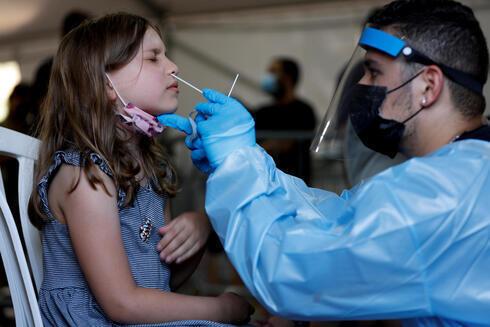 Una niña es sometida a una prueba de detección de coronavirus en un centro de salud de Tel Aviv.