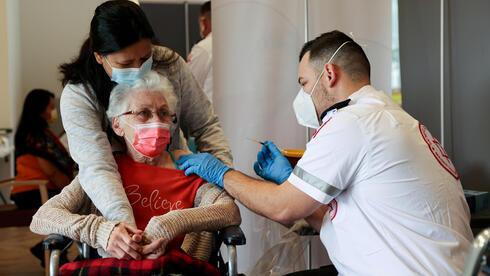 Una mujer recibe una tercera dosis de refuerzo contra el coronavirus en una vivienda asistida en Netanya.