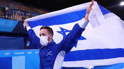 El gimnasta artístico Artem Dolgopyat sostiene la bandera de Israel después de ganar una medalla de oro en los Juegos de Tokio el domingo.