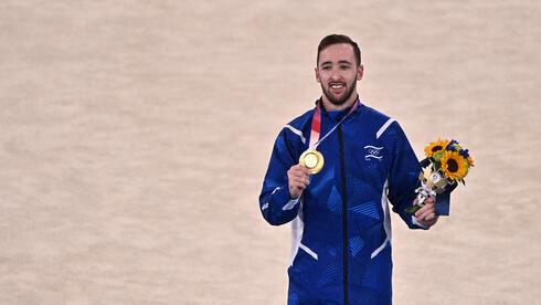 Artem Dolgopyat muestra su medalla de oro en los Juegos de Tokio el domingo.