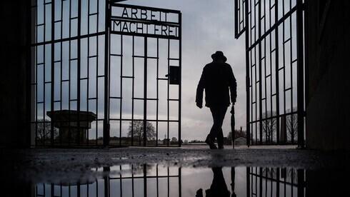 """Un hombre atraviesa la puerta del campo de exterminio nazi de Sachsenhausen con la frase """"Arbeit macht frei"""" (el trabajo te hace libre) en Oranienburg, Alemania."""
