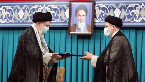 El líder supremo iraní, Alí Jamenei (izquierda), entrega el precepto presidencial al nuevo presidente de Irán, Ebrahim Raisi.