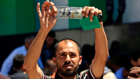 Un ciudadano palestino muestra el dinero entregado como parte de la ayuda de Catar a Gaza.