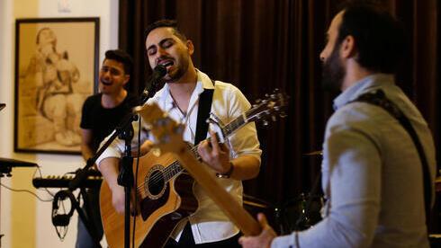 Raji El-Jaru canta y toca la guitarra durante un ensayo de su banda Osprey V en la ciudad de Gaza.