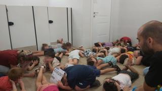 Niños del jardín de infantes del kibutz Dan se arrojan al suelo mientras suena la sirena de alerta.