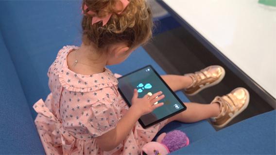 Una niña juega al juego interactivo GiantLeap.