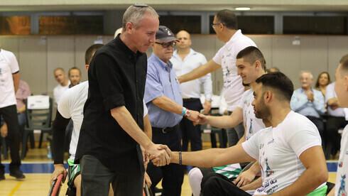 El ministro de Deportes y Cultura, Chili Tropper, saluda a los jugadores tras las finales de baloncesto.