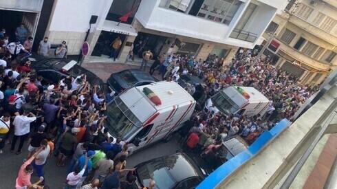 Una multitud y ambulancias en el lugar del ataque.