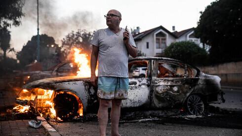 Un residente local permanece junto a su coche en llamas durante los enfrentamientos entre árabes israelíes y la policía en Lod, el 11 de mayo de 2021.