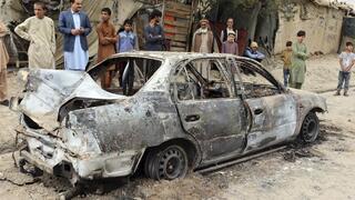 Gente mirando un vehículo dañado por un ataque con un cohete en Kabul, Afganistán.