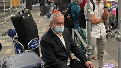 Netanyahu sentado en un carro de equipaje en un aeropuerto de San Francisco de camino a Hawaii.