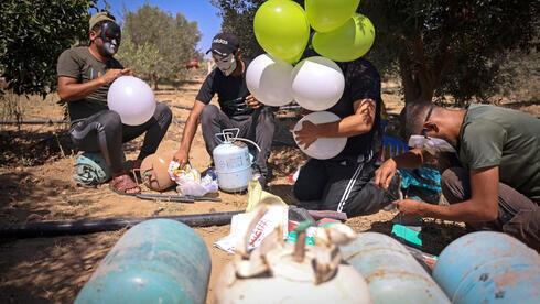 Palestinos enmascarados preparan globos incendiarios para volar hacia Israel.