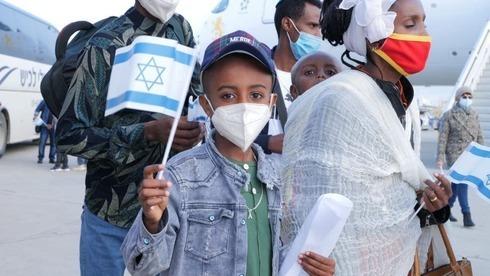 Un inmigrante etíope con la bandera israelí tras aterrizar en el Aeropuerto Ben-Gurion.