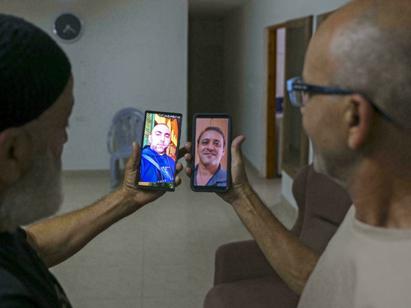 Malek Hassuna, a la izquierda, sostiene su teléfono con una foto de su difunto hijo Mussa, y Effi Yehoshua muestra una foto de su difunto hermano Yigal.