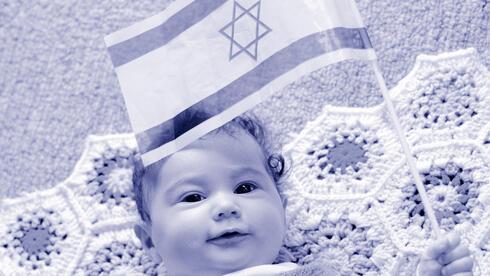 Un bebé sostiene una bandera de Israel.